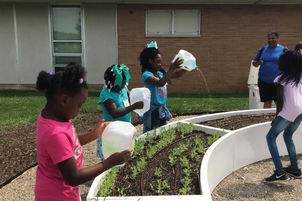 Kids watering garden with reused milk jugs