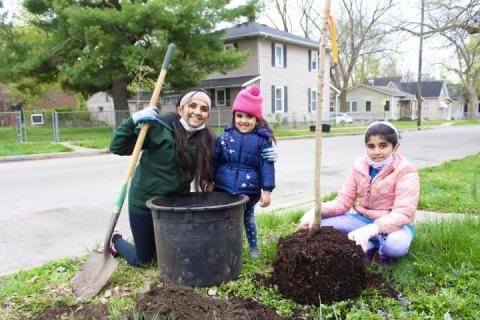 Mother plants a tree with her two daughters for Earth Day.